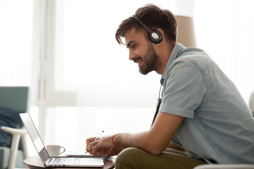 Happy man wearing headset study online on laptop making notes